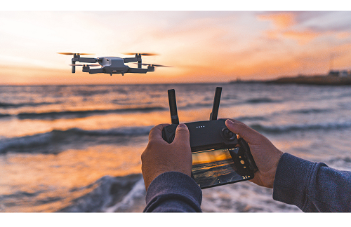 drone hovering over ocean showing hands on controller